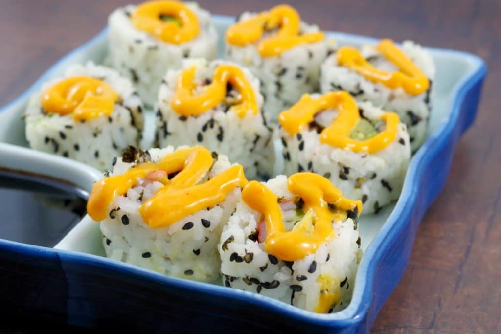 9 california rolls in a sushi dish with sriracha mayonnaise swirled on top