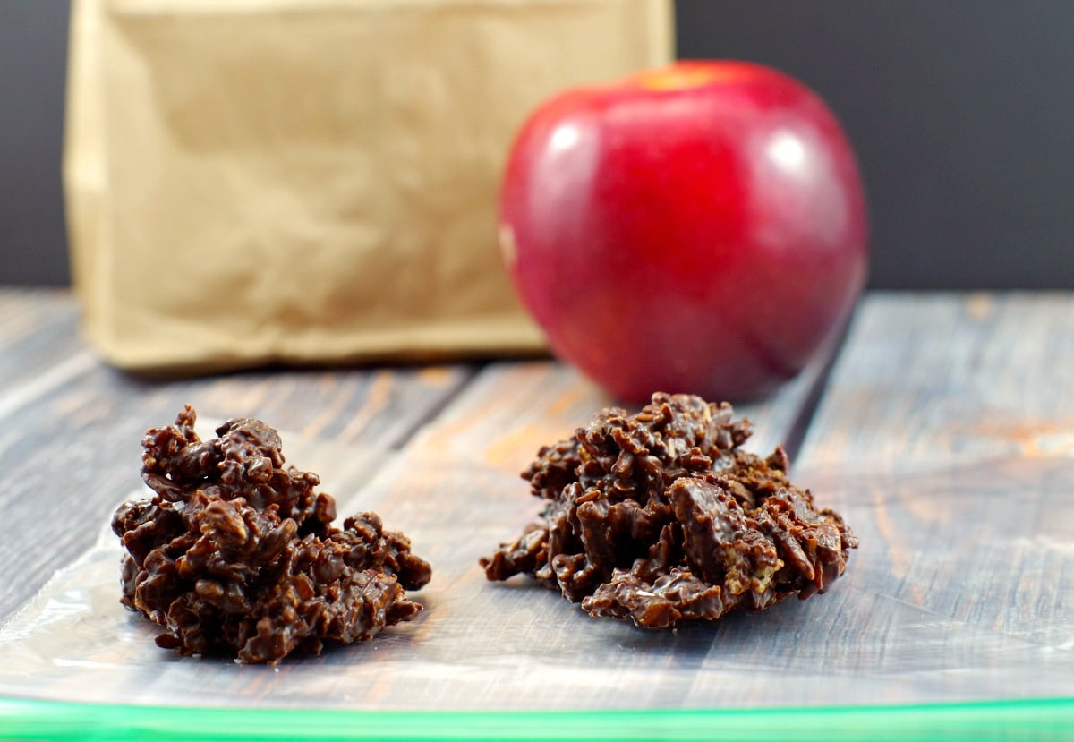 2 chocolate clusters on a ziploc bag with an apple and brown paper lunch bag in the background
