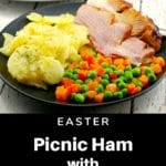picnic ham on a plate with scalloped potatoes and vegetables