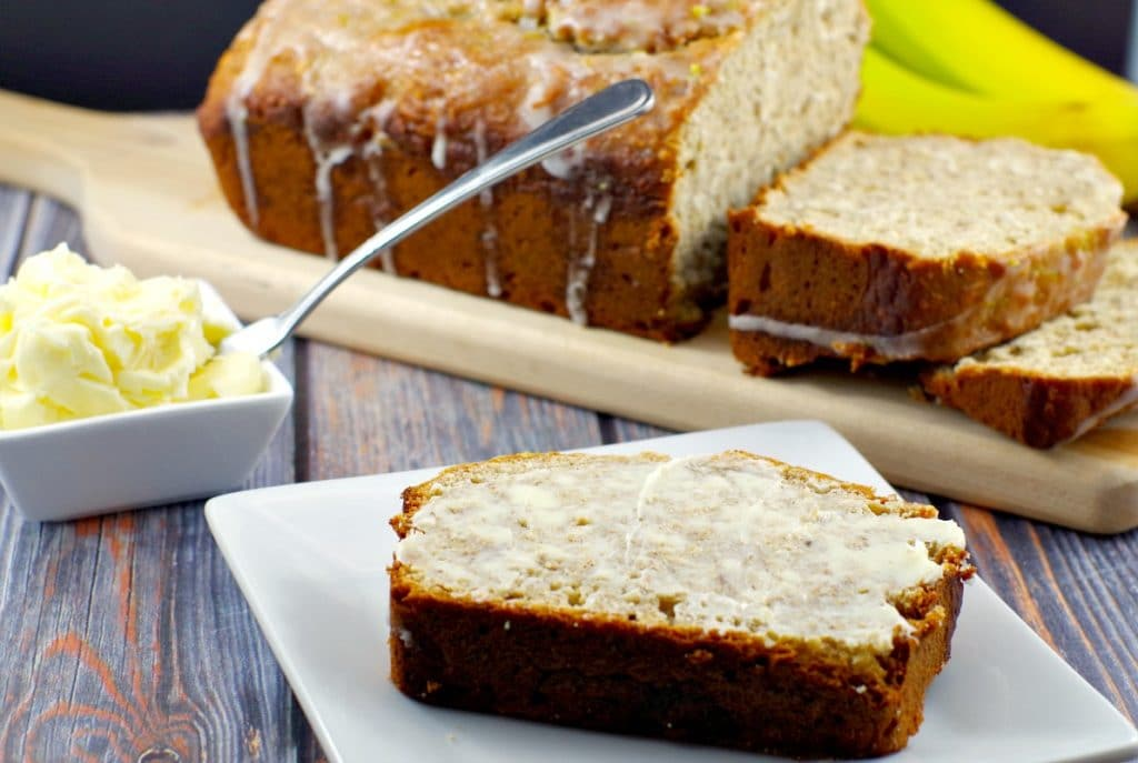 slice of banana bread with butter and sliced banana loaf in background