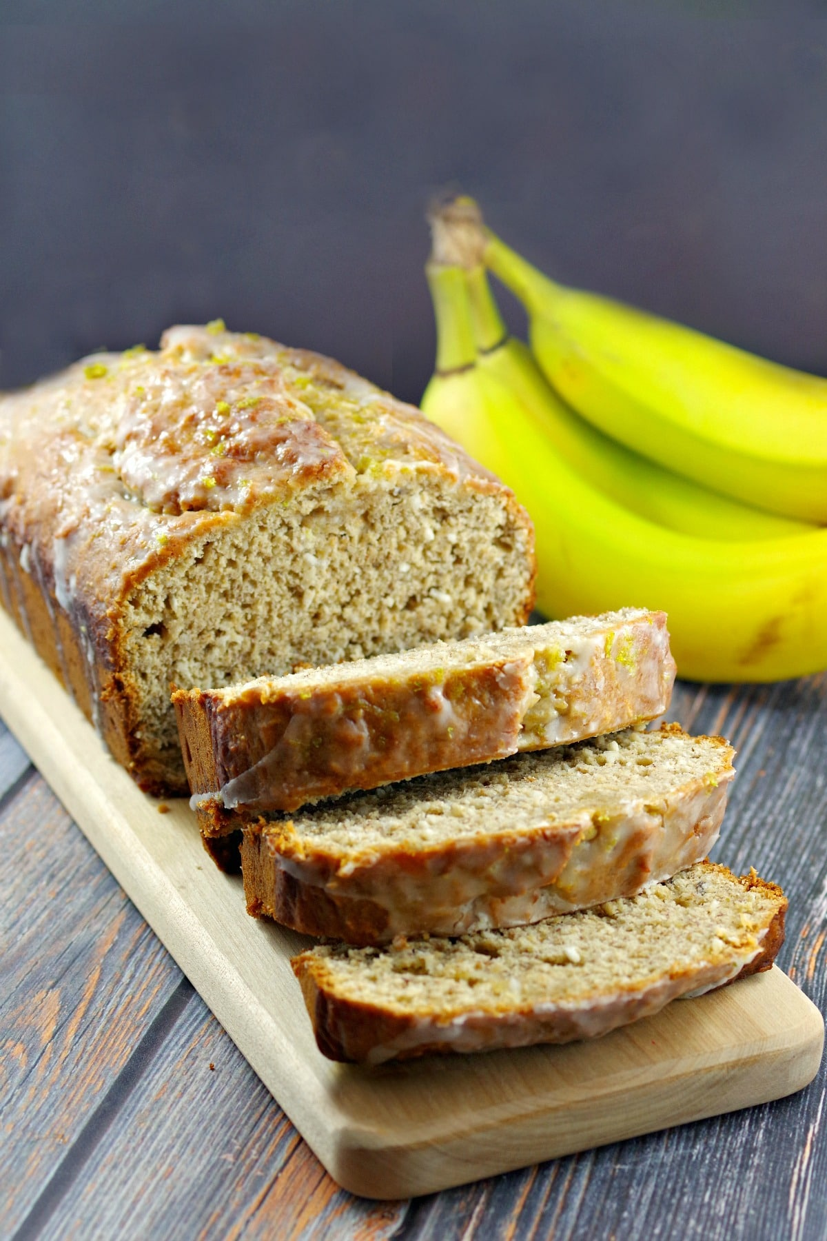 sliced banana bread with bananas in background