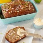Pinterest pin with banana bread in blue loaf pan with slice of banana bread on a wh\ite plate with butter