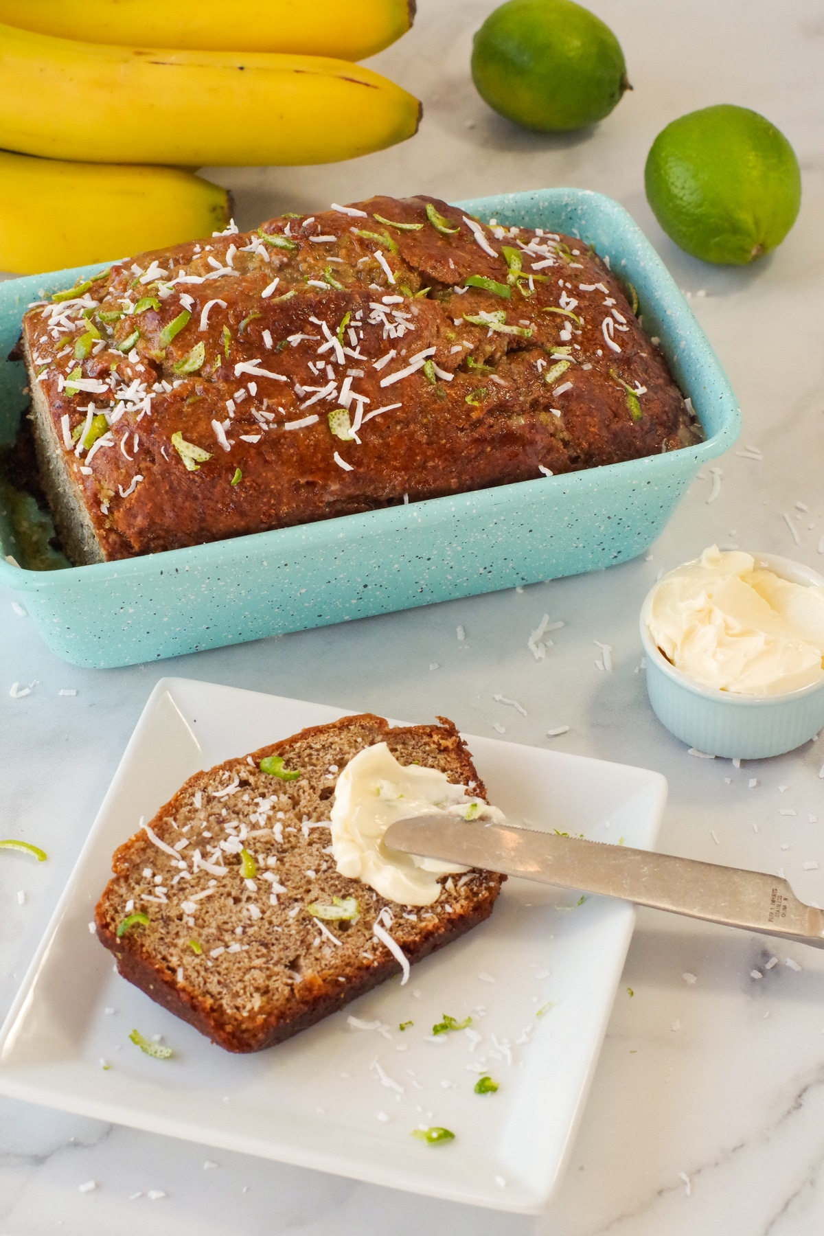banana bread in blue loaf pan with slice of banana bread on a white plate with butter