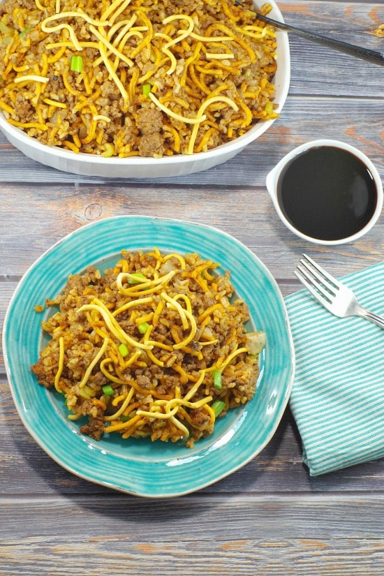 Blue plate with chow mein casserole on it, dish of soya sauce and casserole dish with chow mein casserole in it in background