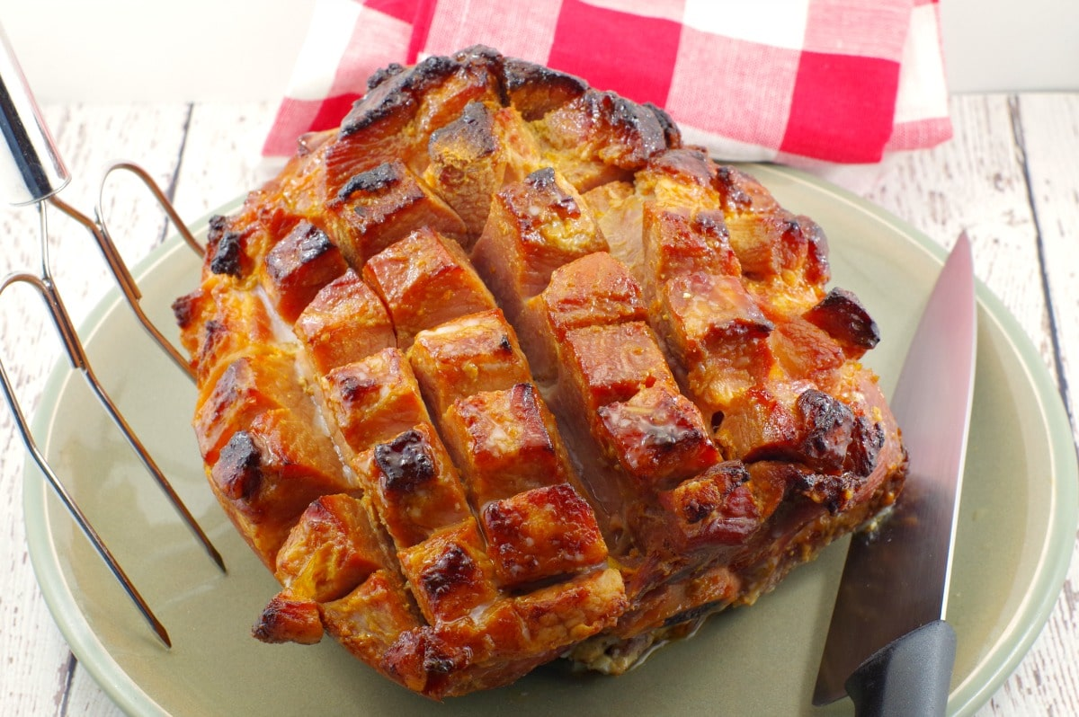 Whole, scored and cooked picnic ham on a plate