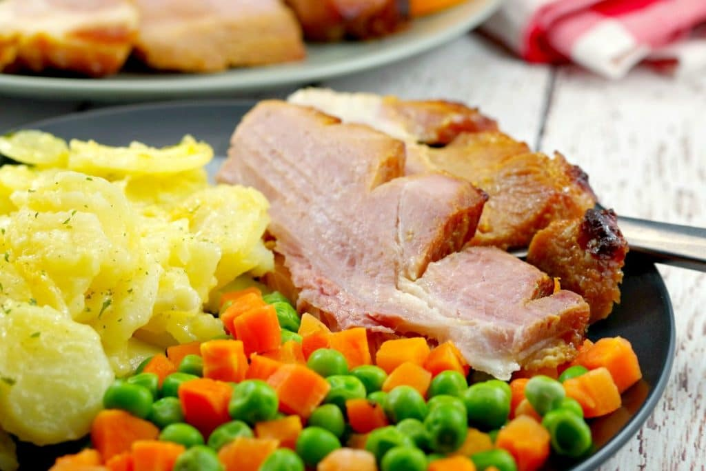 Sliced picnic ham on a plate with scalloped potatoes and veggies with whole ham in background