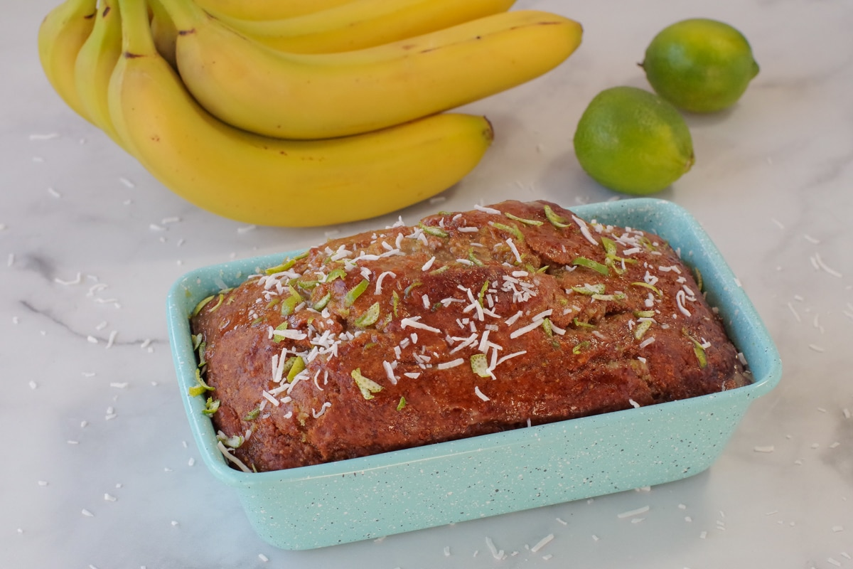 Tropical banana bread in blue loaf pan with bananas and limes in background