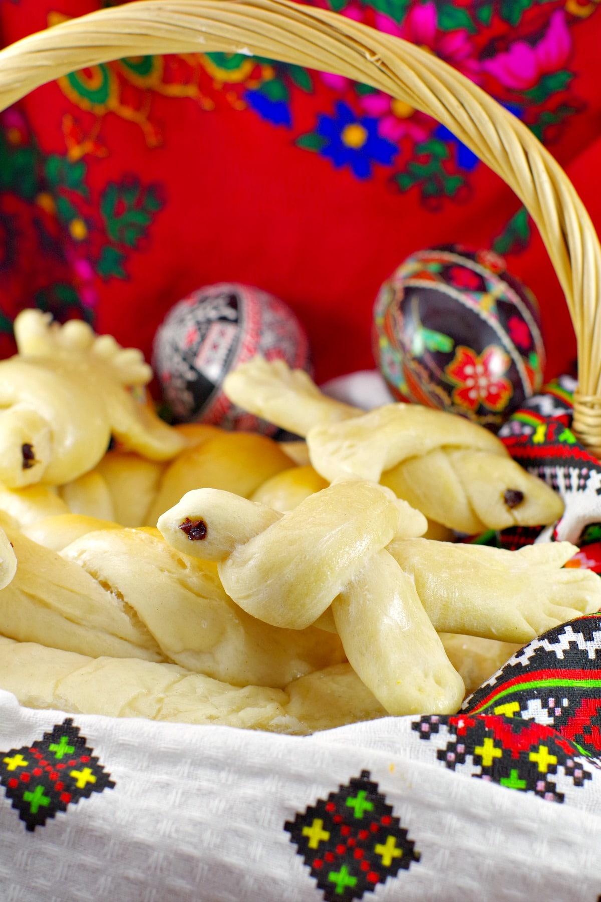 Ukrainian Easter bread doves in basket with Ukrainian Easter Eggs in background