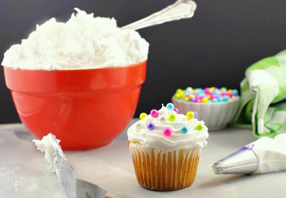 Frosted cupcake with pearl sprinkles, spatula and decorating tip in foreground with orange bowl of frosting and small bowl pearl sprinkles in background