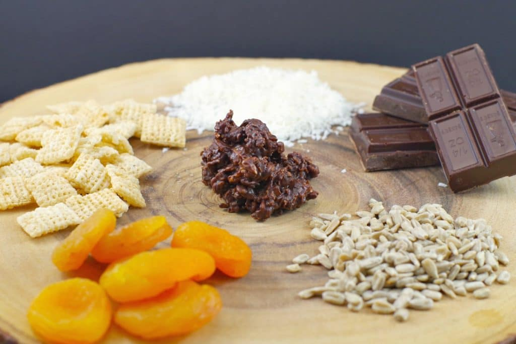 Chocolate cluster in centre surrounded by ingredients (coconut, chocolate, sunflower seeds, chex rice cereal, apricots) on wooden tree tray