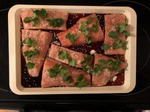 frozen raw salmon fillets on sheet pan with soya sauce, cilantro, sesame seeds and ginger