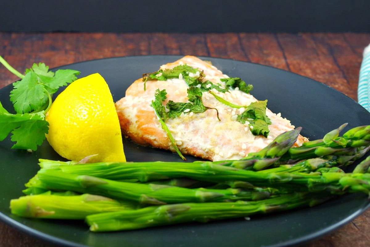 Salmon fillet on a black plate with lemon wedge and steamed asparagus