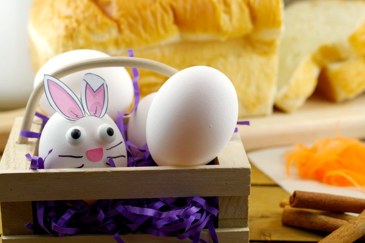 3 Eggs in a basket (one made to look like an Easter bunny) with bread and other french toast ingredients in background