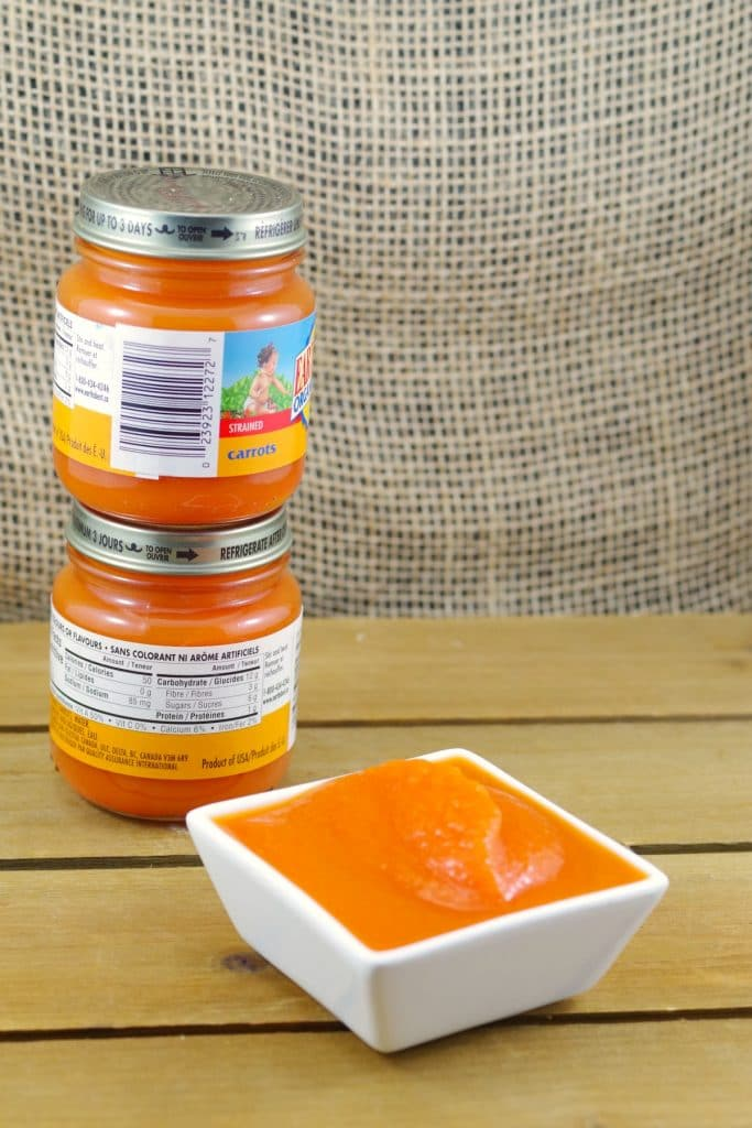 2 jars of baby food piled up behind a dish of carrot baby food