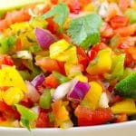 pinterest pin with photo of fresh Pico de Gallo Salsa. garnished with 2 lime wedges, in a white bowl surrounded by nacho chips with white text on black bottom