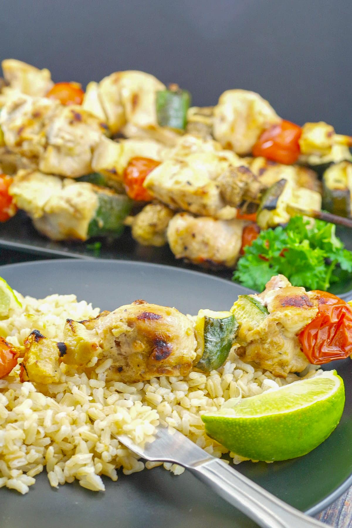 Kabob on rice pilaf with lime and tray of kabobs in background