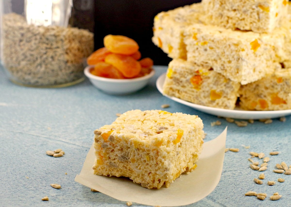 Rice Krispie treat on parchment paper with plate of treats, bowl of apricots and jar of sunflower seeds in the background