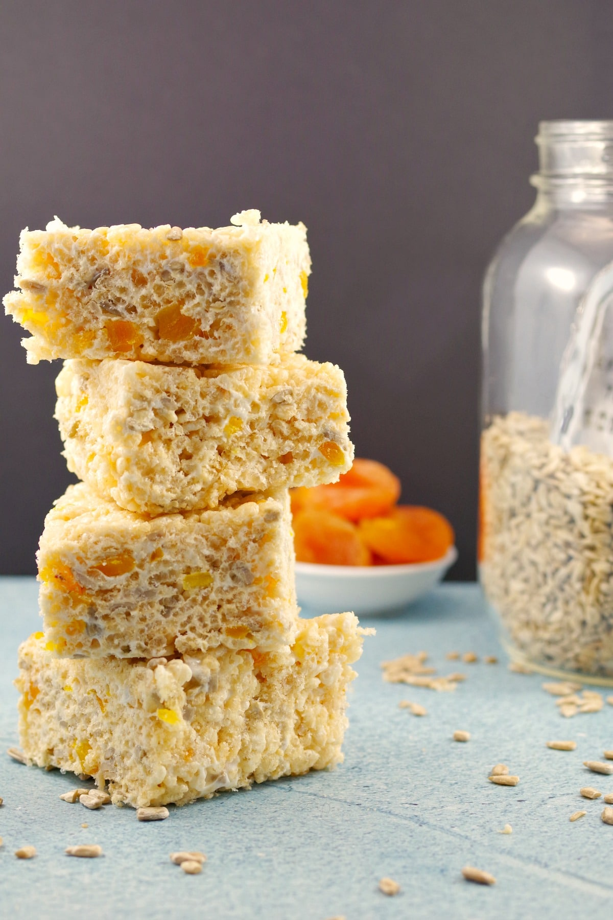 4 Apricot Sunflower Rice Krispie Treats stacked with apricots and sunflower seeds in background