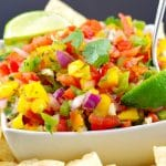 Pico de Gallo Salsa. garnished with 2 lime wedges, in a white bowl surrounded by nacho chips