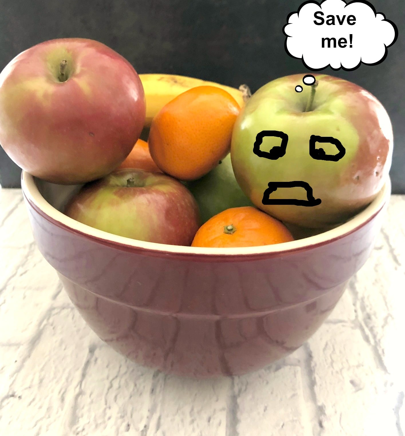 Fruit in a bowl with a word bubble from the apple saying 'save me' and black hand drawn distressed face on apple