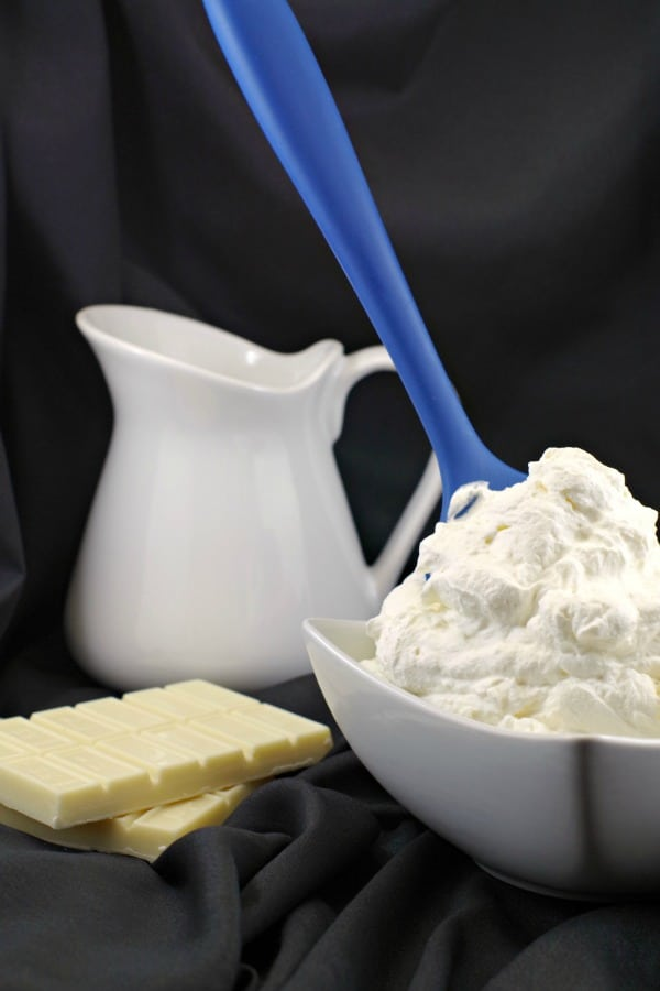 bowl of white chocolate whipped cream frosting with blue spatula handle sticking out and white cream container in background