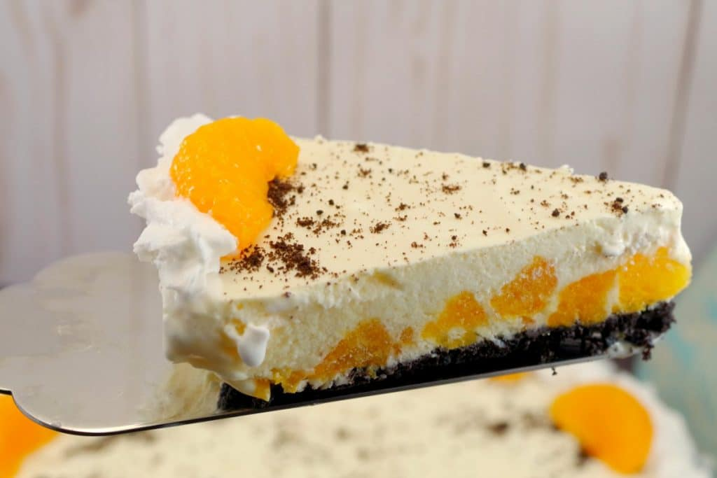 Piece of Dairy-free Orange Dreamsicle Pie being lift out of whole pie with metal pie lifter