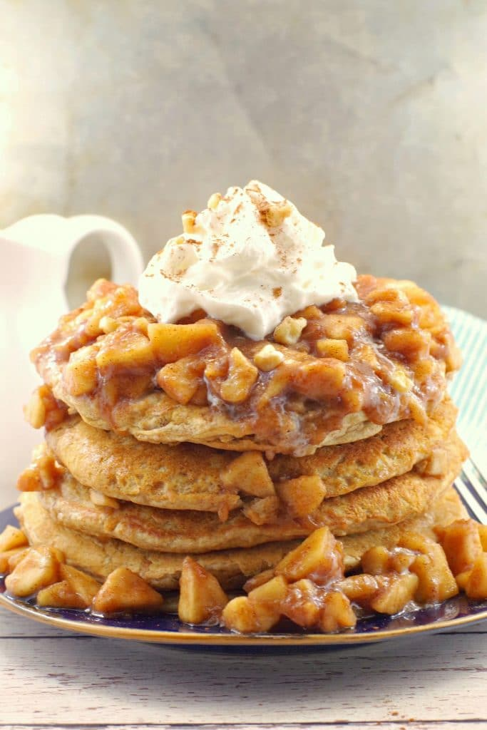 stacked pancakes with apple topping and whipped cream