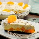 Piece of Orange Creamsicle pie (dairy-free) on white plate with whole pie in background