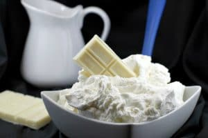 A bowl of white chocolate whipped cream frosting with a bar of baker's white chocolate stuck in frosting