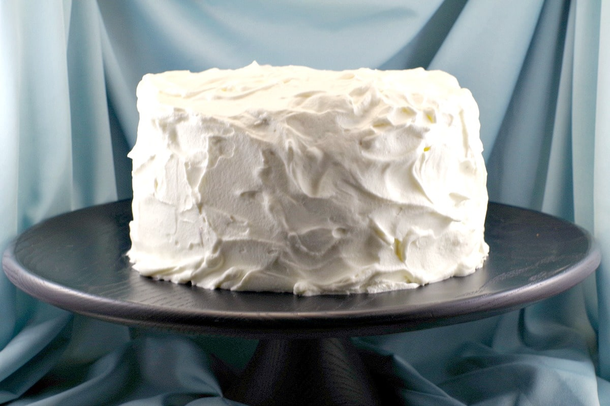 whole cake on black cake stand, covered with white chocolate whipped cream frosting