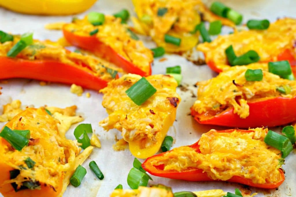 Buffalo Chicken Stuffed peppers on a parchment covered sheet pan