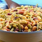 Easy (vegan) mixed bean salad in a large bowl with a dark brown wooden spoon