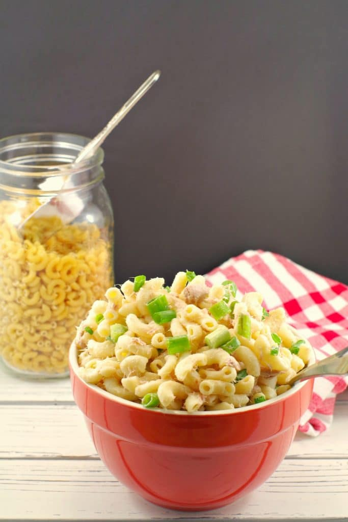 Macaroni salad in red bowl with uncooked macaroni in background