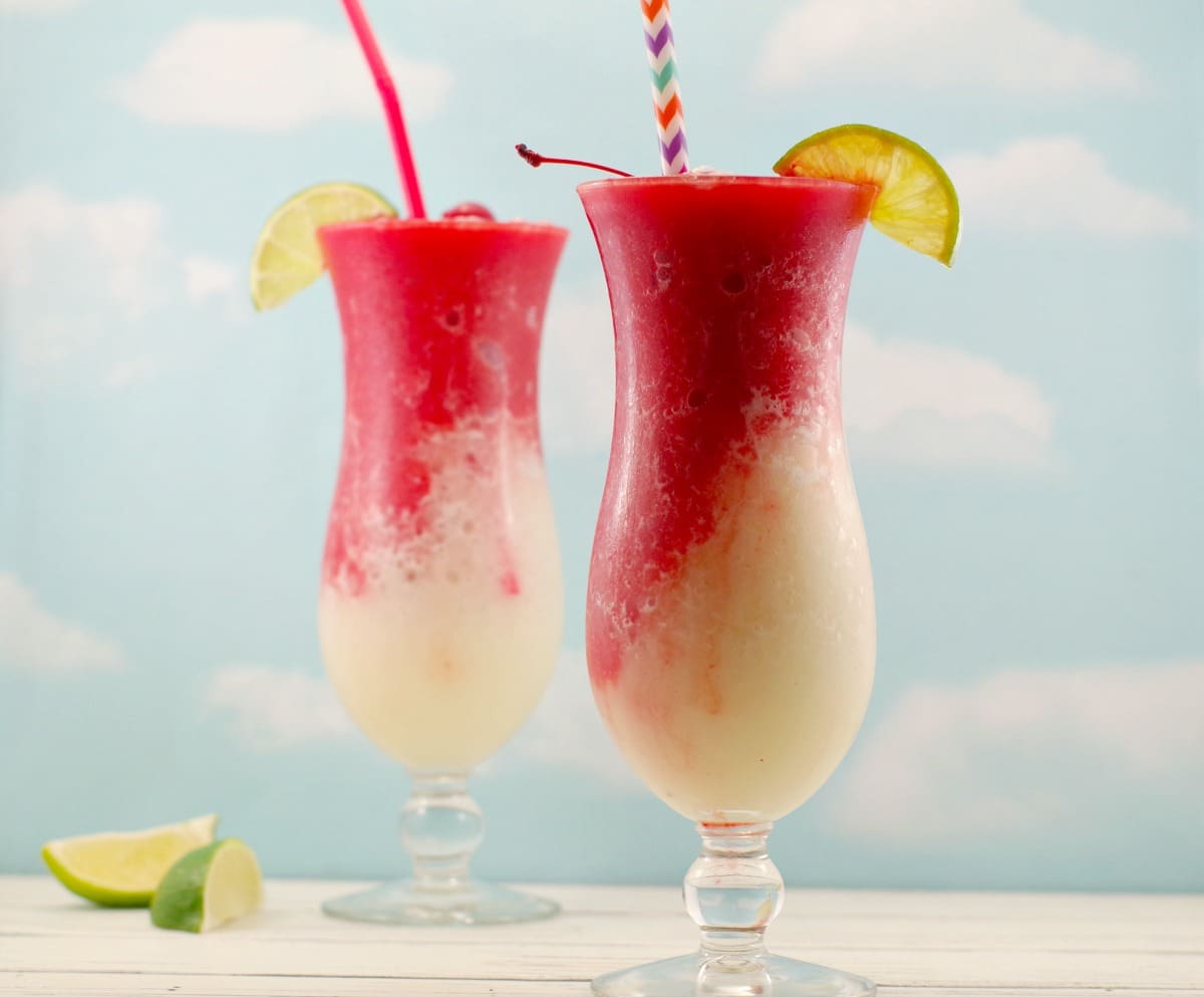 2 Miami Vice Mocktails with straws and lime wedge and cherry garnishes