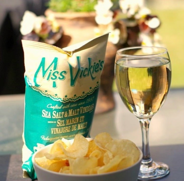 glass of wine with bowl of chips and chip bag behind it
