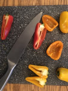 peppers on cutting board with knife