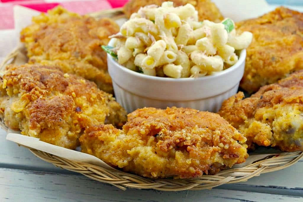 Fried chicken on a plate with bowl of macaroni salad in the middle