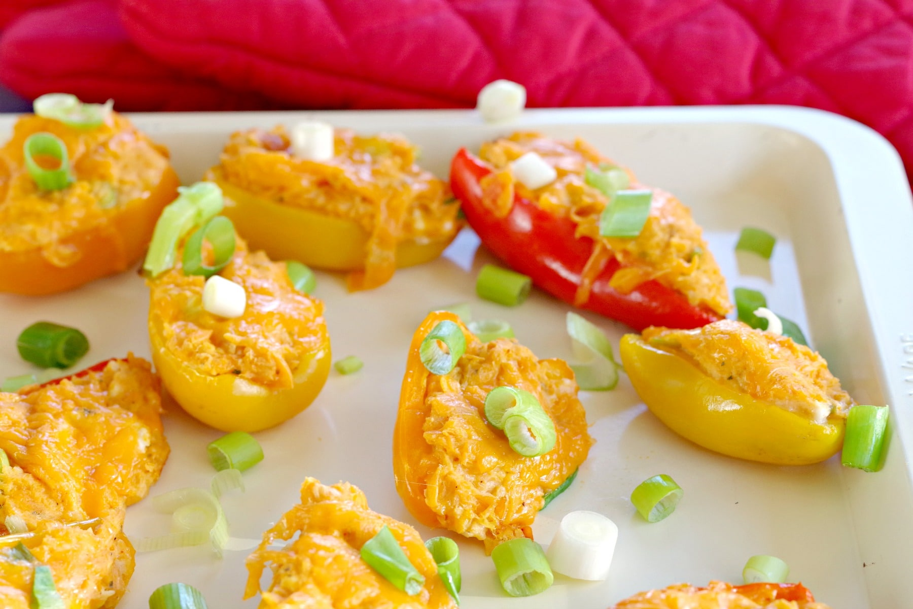 stuffed mini peppers on an off-white baking sheet with red oven mitts in the background