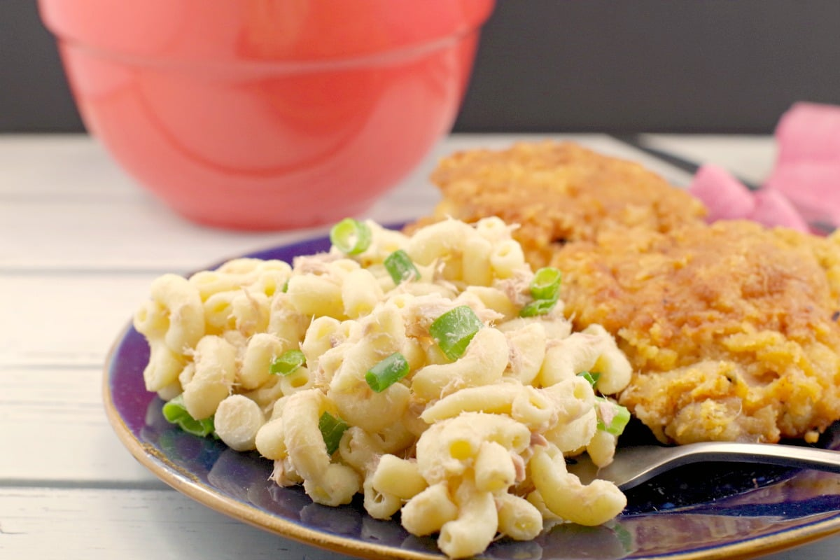 Tuna Macaroni Salad on plate with fried chicken and red bowl of salad in background