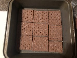 chocolate graham crackers lining bottom of pan