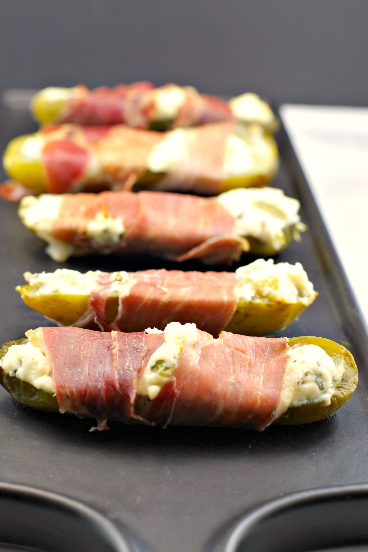 Prosciutto wrapped boursin stuffed pickles on a black tray