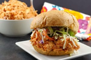 Buffalo Chicken Sandwich on white plate with bowl of shredded buffalo chicken in background