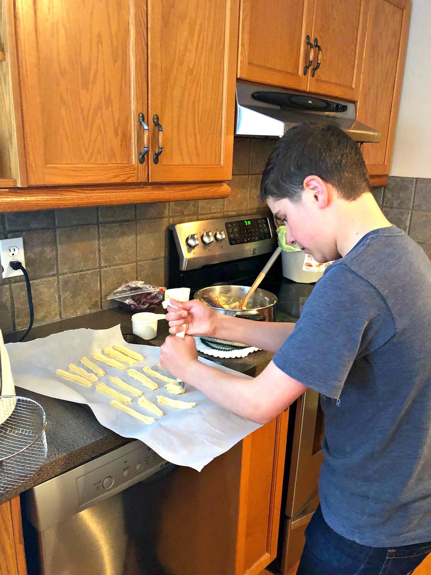 teenage boy making churros