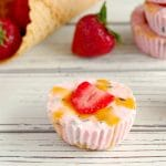 Strawberry Drumstick Frozen Yogurt Cups on white table with strawberries and cones in background