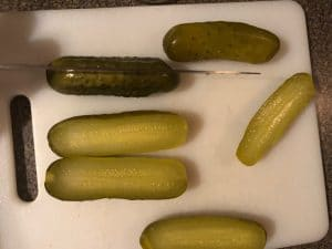 Pickles being sliced in half, lengthwise