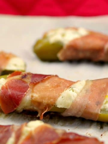 Prosciutto wrapped boursin stuffed pickle on a parchment covered sheet pan
