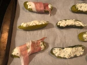 pickles being wrapped in prosciutto