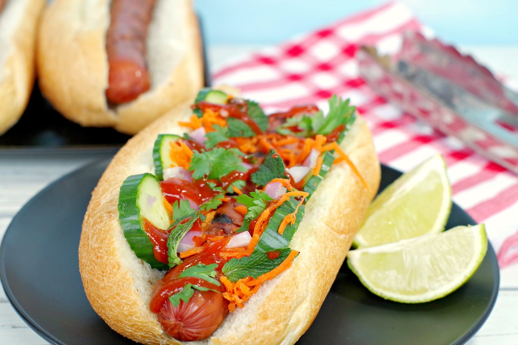 Banh Mi turkey hot dog on black plate with lime wedges