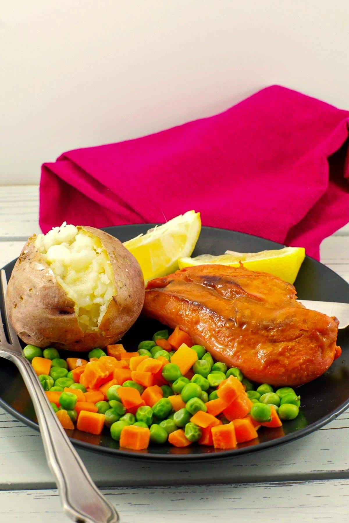 Bonanza Monterey chicken on plate with baked potato and mixed vegetables