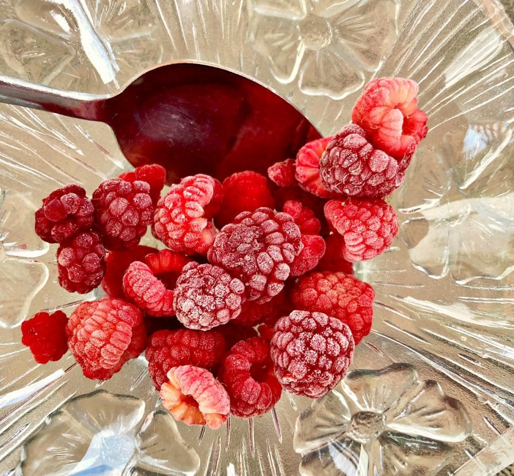 frozen raspberries in glass bowl with spoon